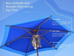 Blue Umbrella With Wooden Patio During Day Time