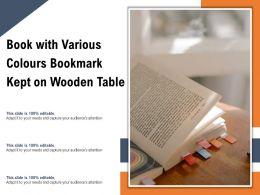 Book With Various Colours Bookmark Kept On Wooden Table