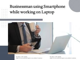 Businessman Using Smartphone While Working On Laptop
