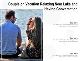 Couple On Vacation Relaxing Near Lake And Having Conversation
