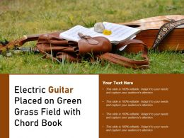 Electric Guitar Placed On Green Grass Field With Chord Book