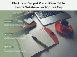 Electronic Gadget Placed Over Table Beside Notebook And Coffee Cup