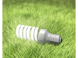 Energy Saving Light Bulb On Green Grass Stock Photo