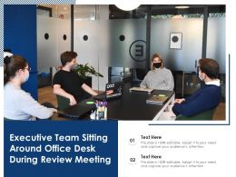 Executive Team Sitting Around Office Desk During Review Meeting
