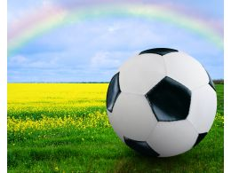 Football Under The Rainbow And Over Grass Stock Photo