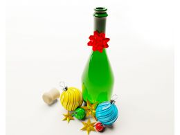 Green Bottle With Colorful Decorative Balls Stock Photo