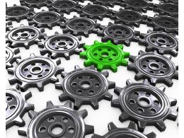Grey Gears With One Green Gear As Leader Stock Photo