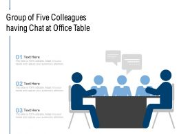 Group Of Five Colleagues Having Chat At Office Table