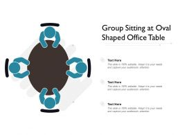 Group Sitting At Oval Shaped Office Table