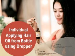 Individual Applying Hair Oil From Bottle Using Dropper