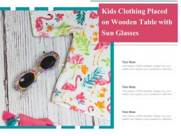 Kids Clothing Placed On Wooden Table With Sun Glasses