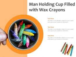 Man Holding Cup Filled With Wax Crayons