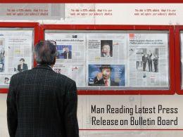 Man Reading Latest Press Release On Bulletin Board