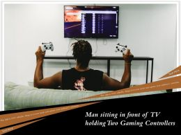 Man Sitting In Front Of TV Holding Two Gaming Controllers