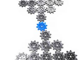 Multiple Gears With One Blue Gear In The Middle As Leader Stock Photo
