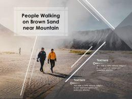 People Walking On Brown Sand Near Mountain