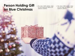 Person Holding Gift On Blue Christmas