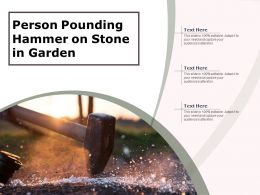 Person Pounding Hammer On Stone In Garden