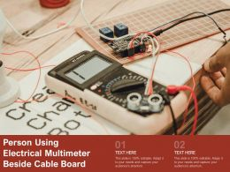 Person Using Electrical Multimeter Beside Cable Board