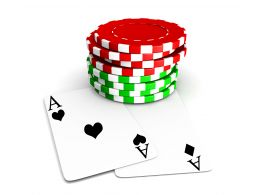 Red And Green Poker Chips With Two Aces Beneath Stock Photo