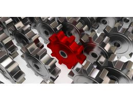 Red Gear In Between Black Gears For Leadership Stock Photo