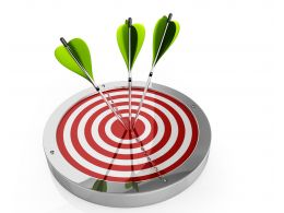 Red Target Board With Green Arrows Hitting Center Stock Photo