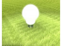 Shiny White Light Bulb On Green Grass Stock Photo