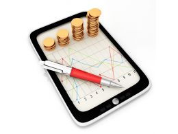 Tablet With Line Chart And Stack Of Gold Coins Stock Photo