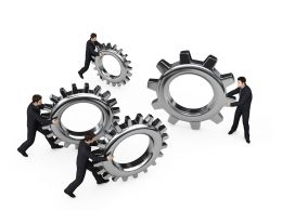 Team Holding Gears In Hand For Process Control Stock Photo