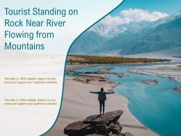 Tourist Standing On Rock Near River Flowing From Mountains