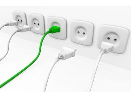 White Multiple Sockets In Line With Plugs And Green Plug For Leadership Stock Photo