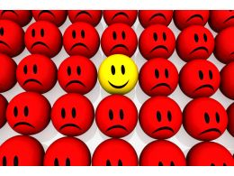 Yellow Happy Smiley Among Red Unhappy Smileys Stock Photo