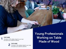 Young Professionals Working On Table Made Of Wood