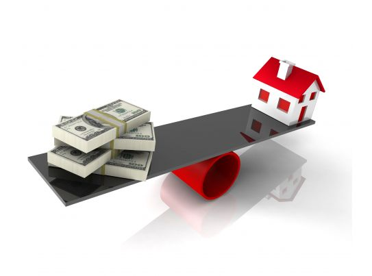 house with balance money on balancing scale stock photo